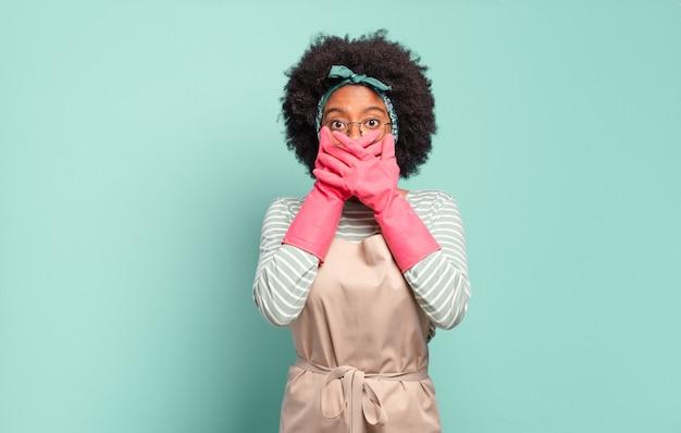 Donna afro nera che copre la bocca con le mani con un'espressione scioccata e sorpresa, mantenendo un segreto o dicendo oops.