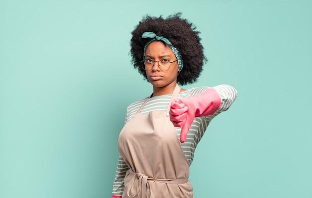 Donna afro nera che si sente arrabbiata, arrabbiata, infastidita, delusa o scontenta, mostrando il pollice verso il basso con uno sguardo serio. concetto di pulizia.. concetto di famiglia