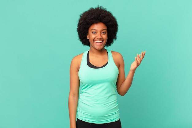 Donna afro nera che si sente felice, sorpresa e allegra, sorridente con atteggiamento positivo, realizzando una soluzione o un'idea