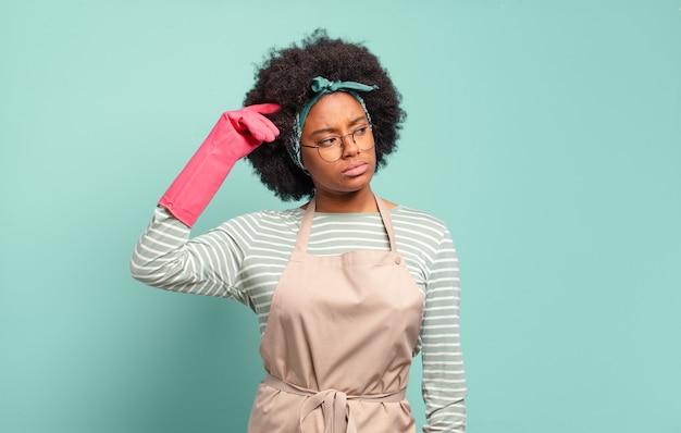Donna afro nera che si sente perplessa e confusa, si gratta la testa e guarda di lato. concetto di pulizia.. concetto di famiglia