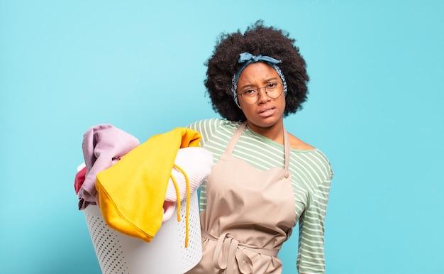 Donna afro nera che si sente perplessa e confusa, con un'espressione stupida e sbalordita che guarda qualcosa di inaspettato. concetto di pulizia.. concetto di famiglia
