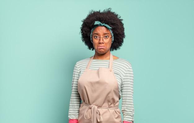 Donna afro nera che si sente triste e piagnucolona con uno sguardo infelice, piange con un atteggiamento negativo e frustrato. concetto di pulizie .. concetto di famiglia