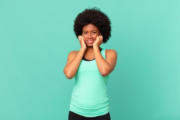 Donna afro nera che sembra arrabbiata, stressata e infastidita, coprendo entrambe le orecchie con un rumore assordante o musica ad alto volume