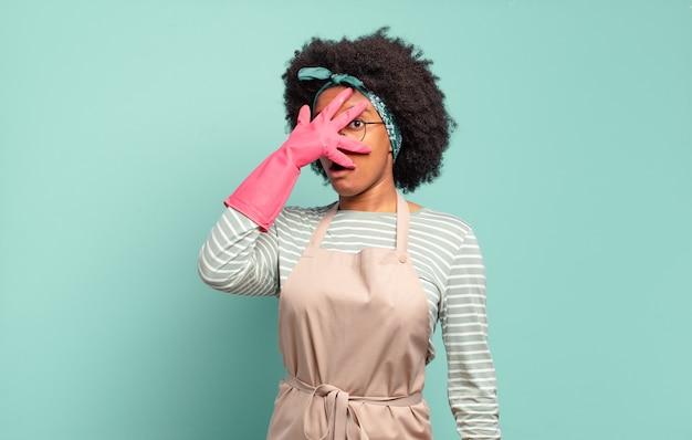 Donna afro nera che sembra scioccata, spaventata o terrorizzata, coprendo il viso con la mano e sbirciando tra le dita. concetto di pulizia.. concetto di famiglia