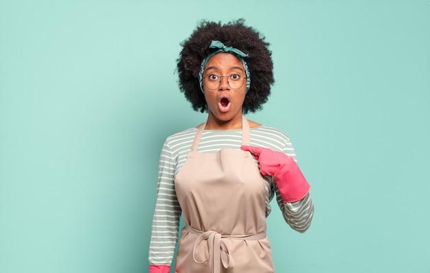 Donna afro nera che sembra scioccata e sorpresa con la bocca spalancata, che indica se stessa. concetto di pulizia.concetto domestico