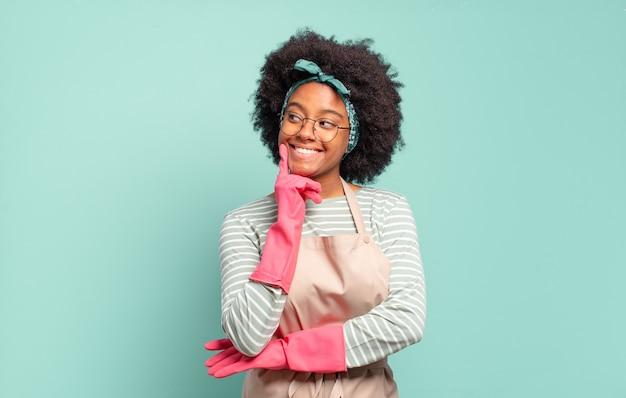 Donna afro nera che sorride felicemente e sogna ad occhi aperti o dubita, guardando di lato. concetto di pulizia.. concetto di famiglia