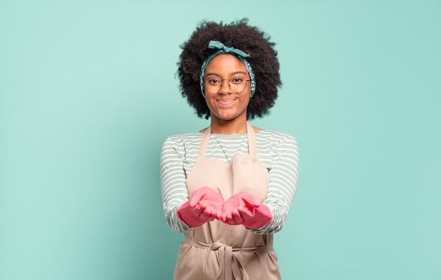 Donna afro nera che sorride felicemente con uno sguardo amichevole, fiducioso e positivo, offrendo e mostrando un oggetto o un concetto. concetto di pulizia.. concetto di famiglia