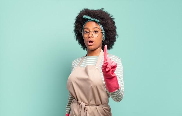 Donna afro nera che sorride con orgoglio e sicurezza facendo la posa numero uno in modo trionfante, sentendosi come un leader. concetto di pulizia.. concetto di famiglia