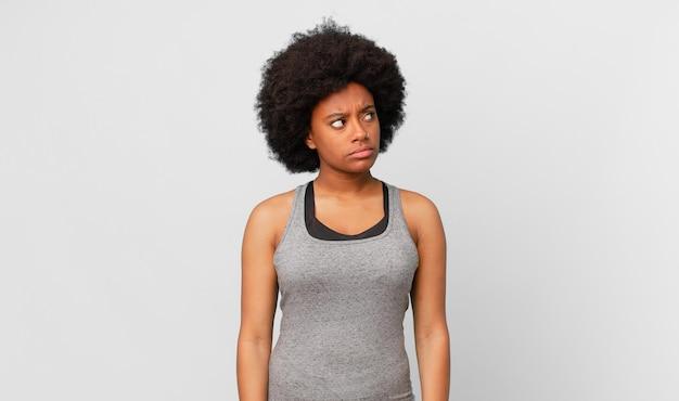 Donna afro nera con un'espressione preoccupata, confusa, senza tracce, guardando in alto per copiare lo spazio, dubitando