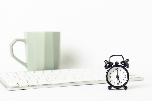 Sveglia nera, una tazza di caffè o tè e una tastiera su una priorità bassa bianca. concetto di ufficio, lavoro al computer, giornata di lavoro, paga oraria.