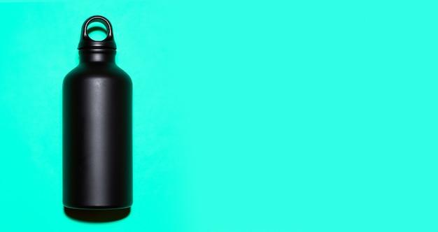 Bottiglia d'acqua termica riutilizzabile in alluminio nero su ciano con spazio di copia.