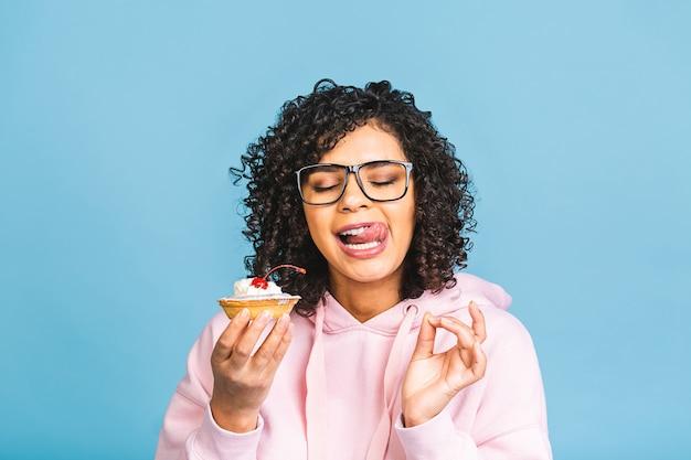 Donna felice afroamericana nera con stile di capelli afro ricci facendo un pasticcio mangiare un dessert fantasia enorme su sfondo blu. mangiare cupcake.