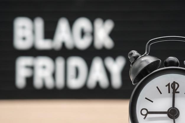 Sveglia analogica nera sullo sfondo del testo inglese venerdì nero