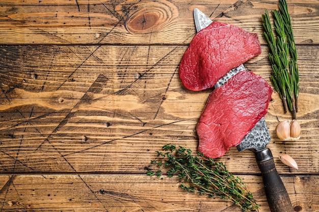 Bistecca di controfiletto di carne di manzo cruda black angus sul coltello da macellaio