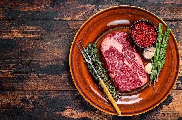 Black angus rib eye bistecca di manzo crudo su un piatto rustico