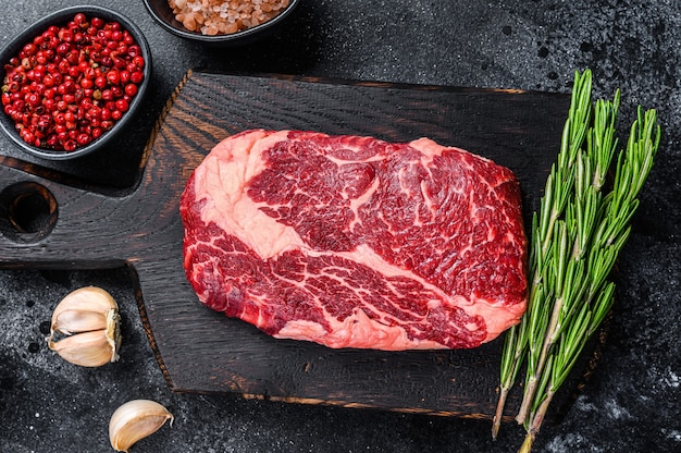 Ribeye di black angus, bistecca di manzo cruda su una tavola di legno con un coltello