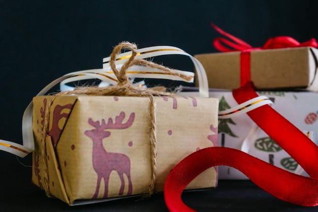 Su uno sfondo nero ci sono i regali di natale avvolti in carta da regalo e legati con nastri, una piccola scatola artigianale legata con un nastro rosso, una grande scatola legata con un nastro bianco d'oro