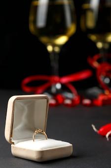 Su uno sfondo nero, una scatola con un anello sullo sfondo bicchieri di champagne e souvenir fuori fuoco. foto verticale
