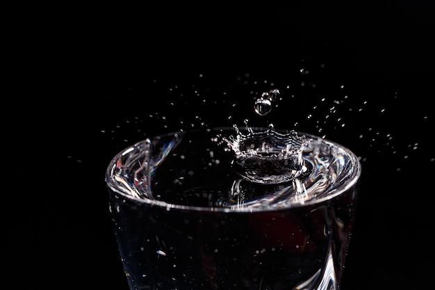 Lo sfondo nero è un bicchiere in cui cade una goccia d'acqua. spruzzi d'acqua sul vetro
