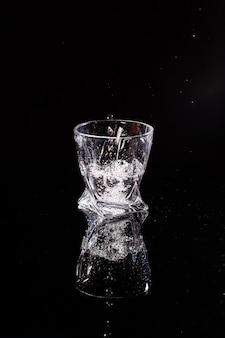 Lo sfondo nero è una scansione in cui l'acqua si riversa. spruzzi d'acqua sul vetro