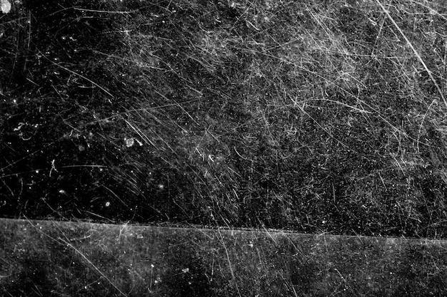 Su uno sfondo nero macchie bianche con graffi. disegno del grunge