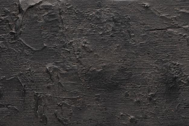 Sfondo nero. legno strutturato con una trama tridimensionale dettagliata, vernice congelata su legno