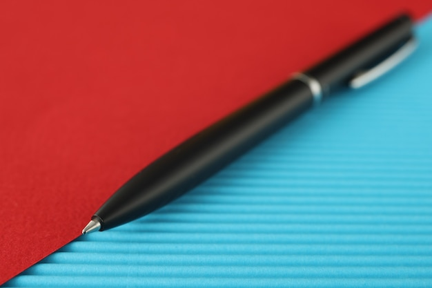 La penna a sfera nera si trova sul concetto blu rosso