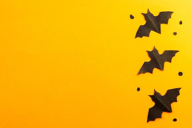 Sagome di pipistrelli neri in carta su sfondo arancione. lay piatto. felice halloween.