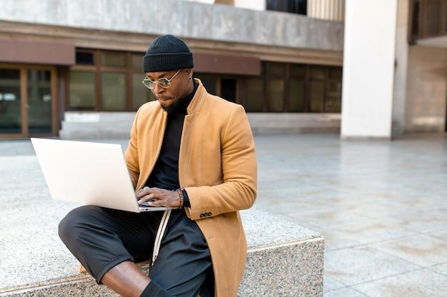 Uomo attraente barbuto nero seduto sui gradini utilizzando il computer portatile in città.