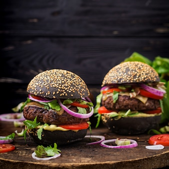 Grande panino nero - hamburger nero con succulenti hamburger di manzo, formaggio, pomodoro e cipolla rossa sulla superficie nera