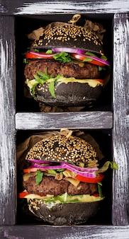 Grande panino nero - hamburger nero con succulenti hamburger di manzo, formaggio, pomodoro e cipolla rossa in scatola sulla superficie nera. disteso. vista dall'alto