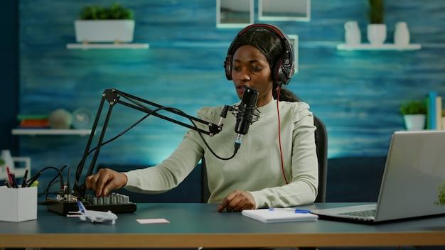 Donna blogger nera che registra video per il suo blog in home studio leggendo messaggi che controllano l'audio sul mixer. trasmissione online di produzione in onda su internet mostra l'host in streaming di contenuti live per i social media