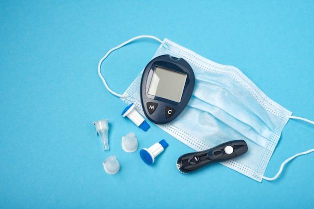 Misuratore di glicemia nero e maschera facciale su sfondo blu, aghi di ricambio per la siringa rchka e lancept, protezione contro i virus delle persone a rischio
