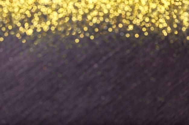 Nero sfocato con paillettes dorate, luci bokeh.