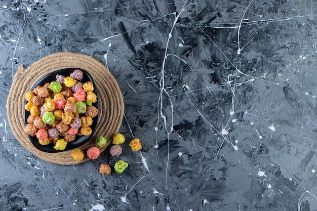 Ciotola nera di popcorn gustosi colorati sulla superficie di marmo.