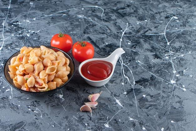 Ciotola nera di gustosa pasta di conchiglie con ketchup sulla superficie di marmo.