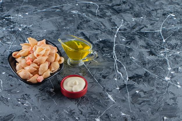 Ciotola nera di gustosa pasta di conchiglie con olio d'oliva su superficie di marmo.