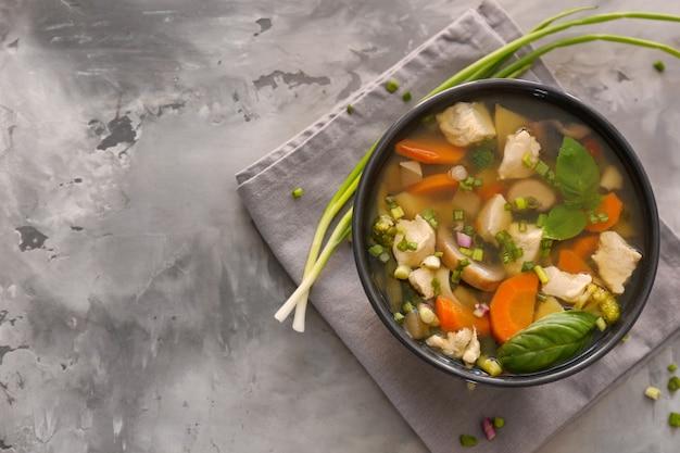 Ciotola nera con deliziosa zuppa di tacchino sul tavolo grigio Foto Premium