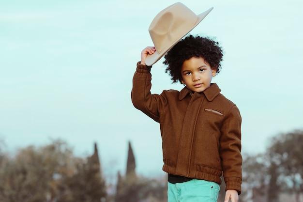 Ragazzo nero che toglie un cappello da cowboy, distogliendo lo sguardo. in un parco sullo sfondo. . immagine con copyspace. concetto di bambini e persone di colore