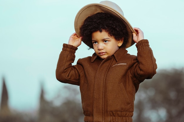 Ragazzo nero che indossa un cappello da cowboy, guardando lontano. in un parco sullo sfondo. . immagine con copyspace. concetto di bambini e persone di colore