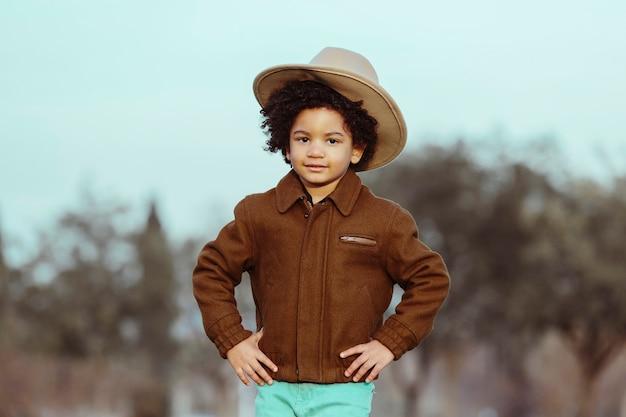 Ragazzo nero con cappello da cowboy. in un parco sullo sfondo. . immagine con copyspace. concetto di bambini e persone di colore