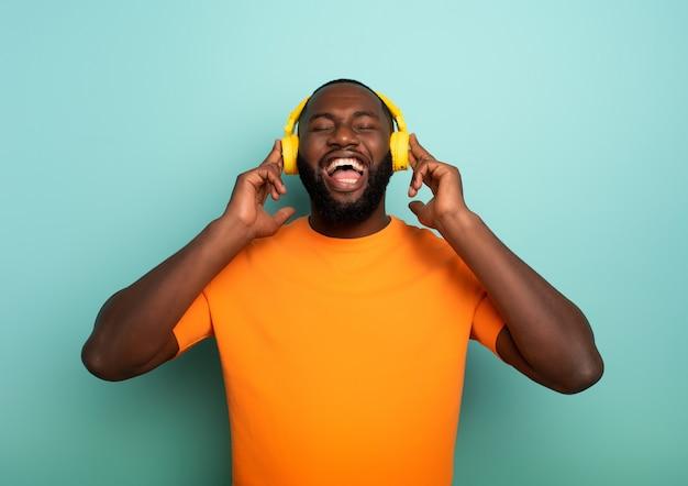 Il ragazzo nero con la cuffia avricolare gialla ascolta musica e balla