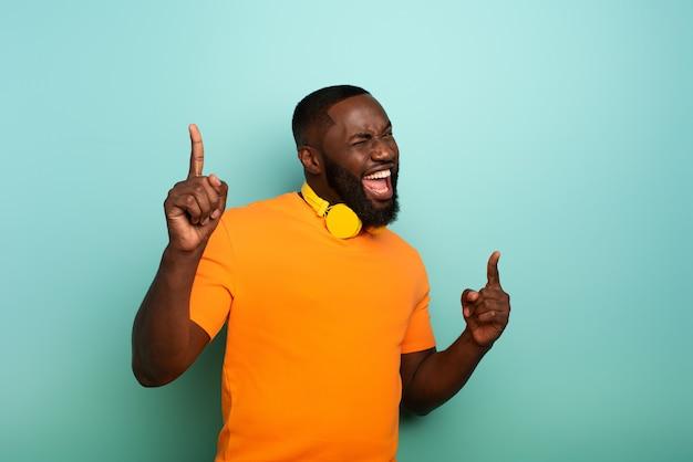 Il ragazzo nero con la cuffia avricolare gialla ascolta musica e balli