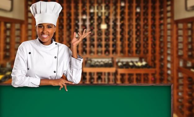 Cuoco unico brasiliano nero della donna che cucina che guarda l'obbiettivo con il bordo verde nello spazio vago della casa del vino.