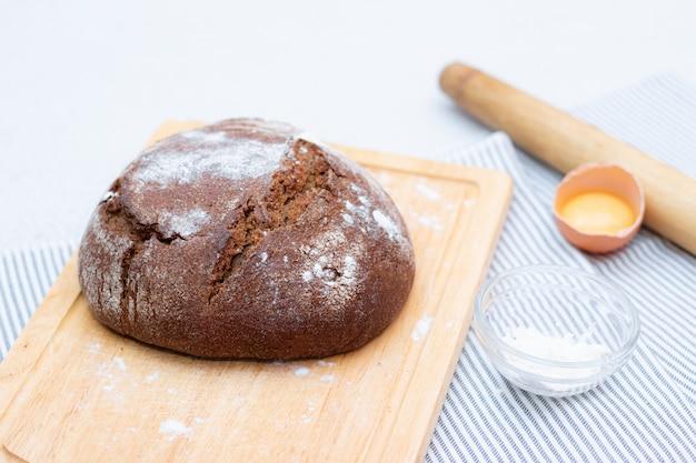 Pane nero. torta fatta in casa. il pane nero è cosparso di farina. segale artigianale fatta in casa appena sfornata e pane di farina bianca. la vista dall'alto.