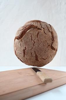 Pane nero su tavola di legno e sfondo bianco. levitazione.