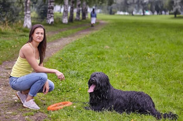 Black briard è sdraiato su una radura in un parco pubblico con una giovane donna vicino a lui.