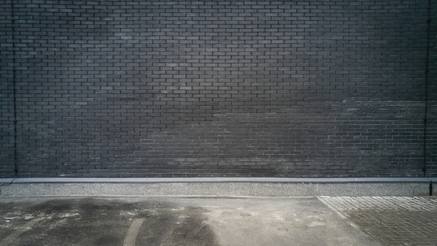 Muro di mattoni neri e pavimento in cemento