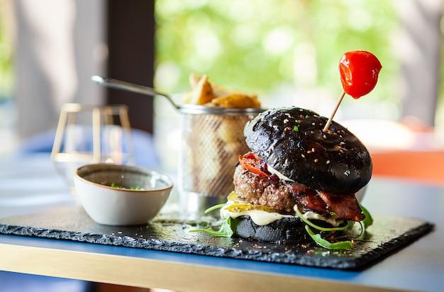 Hamburger nero realizzato dallo chef con patatine fritte nel ristorante