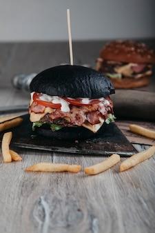 Hamburger nero con carne su tavola rotonda in legno con ascia